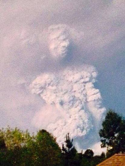 Share International June 2015 images, During the huge eruption of the Calbuco volcano in Chile, in April 2015, a heavy plume of dark grey smoke and ashes took the shape of a gigantic human being