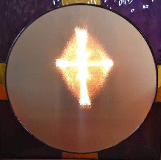This cross of light was discovered in a pane of glass in the Greenwood Community Church in Elk, California by a local Share International co-worker in 1995 when he was checking to make sure the church's lights were working properly. The church is used by the local Share International group for Transmission Meditation. This cross of light was one of three found in the church. Benjamin Creme's Master confirmed that the crosses were energized by Maitreya when they were discovered. The panes of glass remain in the church – one mounted as part of a stained glass window display, and another mounted inside a box. During Transmission Meditation in the church, a light is turned on behind the panes of glass, making the crosses of light visible.