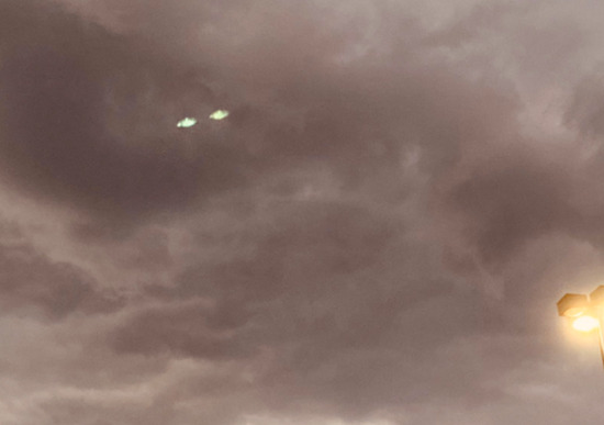 Share International November 2020 images, On 7 October 2020, a resident in West Nyack, New York, took several pictures in succession of an unusual cloud formation. When the pictures were reviewed later, two greenish, glowing, disc-shaped aerial objects were present in one of the photos.