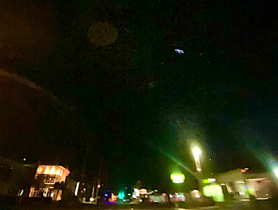 Share International March 2021 images, a lighted, disc-shaped aerial object at low altitude is present in this photo, only one of many taken of the sky.